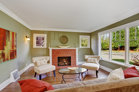 Olive tone family room with fireplace, two white chairs, sofa and glass top coffee table photo