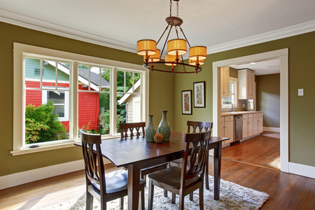 Dining room with wooden table set and rug on the hardwood floor. Room with green walls and white trim