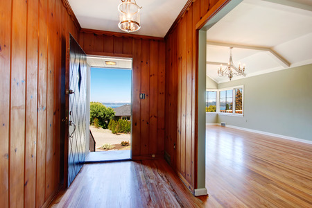 Empty house interior. Entrance hallway with wood plank paneled walls and hardwood floor photo