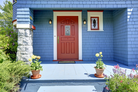 Blue entrance porch with contrast red door. Clapboard siding house with stone trimmed column Foto de archivo
