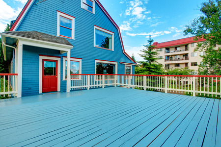 white trim: Blue house with large walkout deck. Deck with blue floor and white railings with red trim