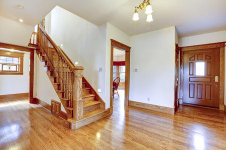 hardwood: Empty house interior. Entrance hallway with new shiny hardwood floor and staircase