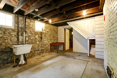 trim wall: Basement empty room interior with stone wall trim and brick wall with fireplace. Room with old sink Stock Photo