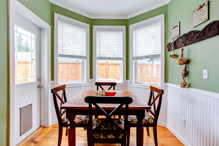white trim: Dining room in light mint color with white trim. Dining table set . Room has exit to backyard Stock Photo