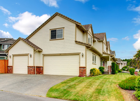 garage on house: Large house with garage and driveway. View of front yard landscape