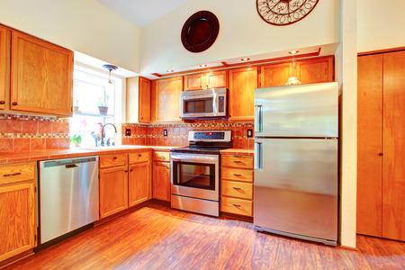 appliances: Kitchen room with orange tile back splash trim, maple cabinets and steel appliances
