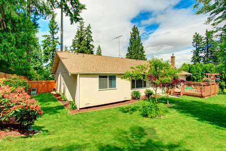 fenced: Fenced back with green lawn and  trees. Backyard landscape design. House with wooden walkout deck