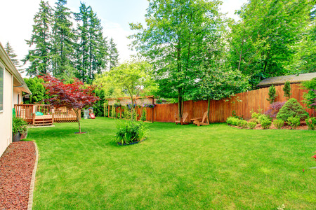 Fenced backyard with green lawn, flower beds and romantic sitting area with wooden chairs and table. Backyard landscape design. House with wooden walkout deck Standard-Bild