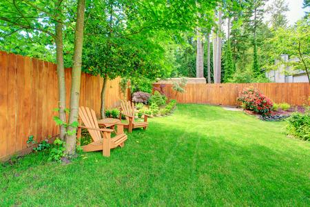 Omheinde achtertuin met groene gazon, bloembedden en romantische zithoek met houten stoelen en tafel Stockfoto