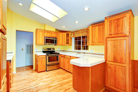 skylights: Countryside house  kitchen room interior. Maple cabinets with white counter top, light yellow walls, hardwood floor and vautled ceiling with skylight