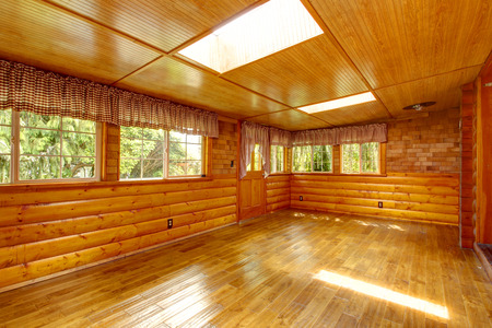 Bright empty log cabin house interior with hardwood floor, skylights and windows