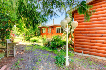 Log cabin style house exterior with grassy walkway and old lantern photo