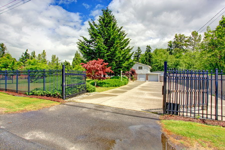 open gate: House exterior with open iron gate, driveway and garage Stock Photo