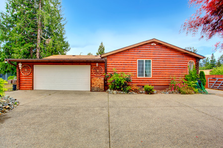 american house: Log cabin style house exterior with garage. House decorated with wooden wheels. Backyard veiw Stock Photo