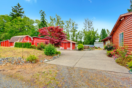 sheds: Log cabin style house exterior with farm sheds in bright red color. Backyard view