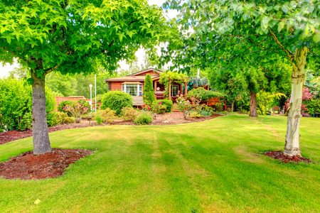 flower bed: Log cabin style house exterior with flower bed and garden Stock Photo