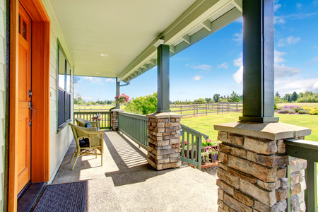 front porch: House walkout deck with railings, stone column base trim and sitting area with wicker chairs
