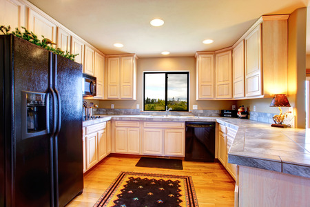 black appliances: Kitchen room with light tone cabinets, black appliances, hardwood floor and rug on it