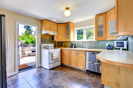 Modern light tone kitchen cabinets with white stove and steel dishwasher. Kitchen with brown tile floor and exit to walkout deck Stock Photo