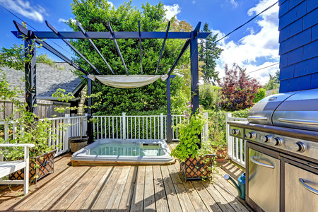 patios: Walkout deck  with jacuzzi and pergola. Patio area with barbecue Stock Photo