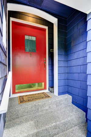 Clapboard siding house in blue color. Entrance porch with bright red door Stock Photo
