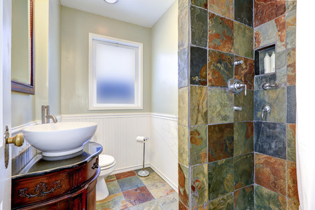 Bathroom interior. Shower with tile wall trim, carved wood cabinet with vessel sink and toilet