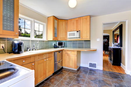 Modern light tone kitchen cabinets with steel dishwasher. Kitchen with brown tile floor and tile back splash trim