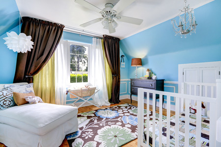 Bright cheerful nursery room interior with blue walls and hardwood floor. Room has crib, settee and cabinet