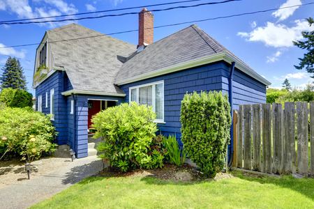 Clapboard siding house in blue color with tile roof and brick shimney Stock Photo