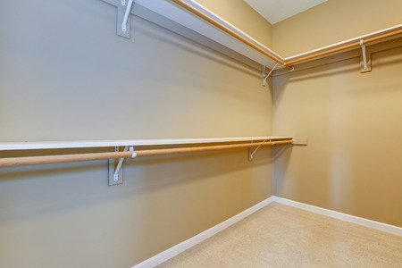 walk in closet: Empty walk-in closet with beige carpet floor and shelves attached to the wall
