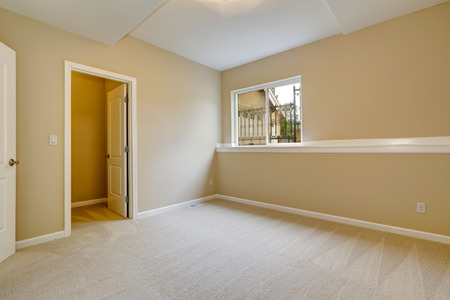 walk in closet: Bright empty bedroom in light ivory tone with carpet floor and small window. Room with walk in closet Stock Photo