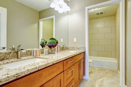 brown granite: Bathroom interior with  tile floor and tile wall trim. Brown modern vanity cabinet with drawers and granite top