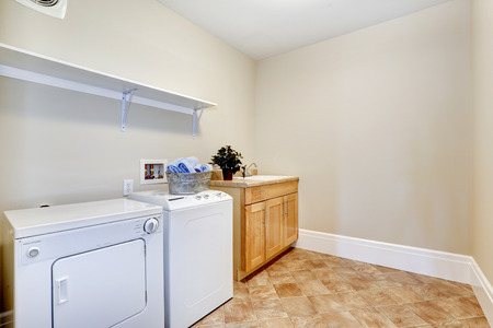 dryer  estate: Laundry room with white appliances and wooden cabinet. Brown tile floor and ivory walls Stock Photo
