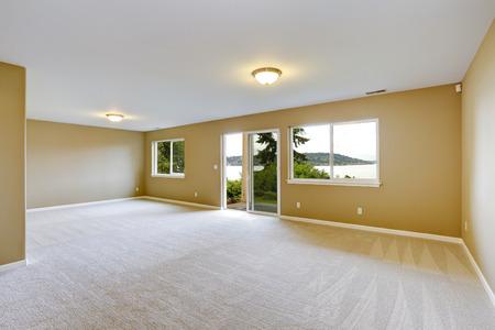 空の家のインテリア。広々 としたファミリールームきれいなカーペットの床とストライキ テラスへの出口