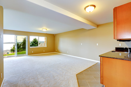 floor covering: Empty house interior. Spacious family room with kitchen cabinets. Room with two type floor covering and walkout patio