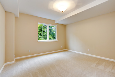 Bright empty bedroom in light ivory tone with carpet floor and small window Stok Fotoğraf
