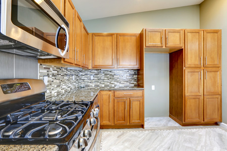 vaulted ceiling: Luxury kitchen room with bright brown cabinets, mosaic backsplash trim and streel appliances.