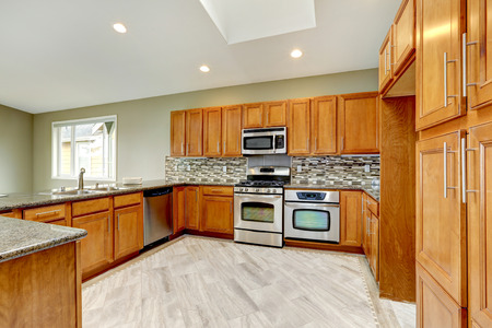 cabinets: Luxury kitchen room with bright brown cabinets, mosaic backsplash trim and streel appliances.