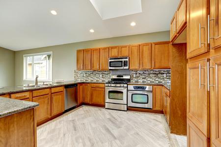 kitchen cabinets: Luxury kitchen room with bright brown cabinets, mosaic backsplash trim and streel appliances.