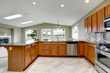 kitchen tile: Luxury kitchen room with bright brown cabinets, mosaic backsplash trim and streel appliances.