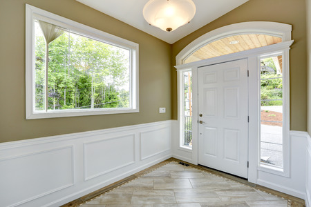 trims: Entrance hallway with tile floor and beige wall with white trim. White door with arch and windows Stock Photo