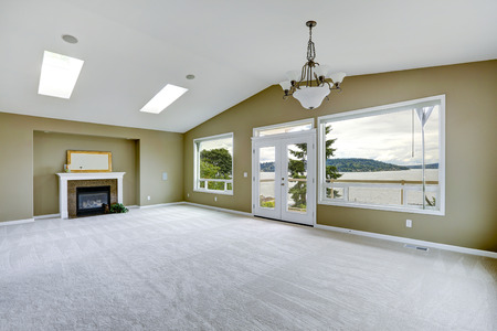 Empty spacious living room with walkout deck and fireplace. Room with high vaulted ceiling and skylights. photo