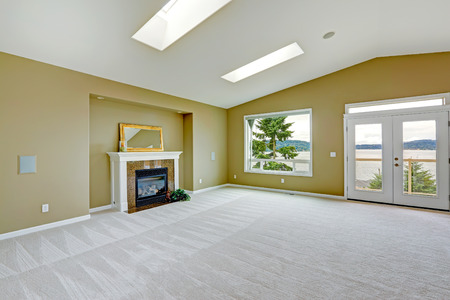 Empty spacious living room with walkout deck and fireplace. Room with high vaulted ceiling and skylights.