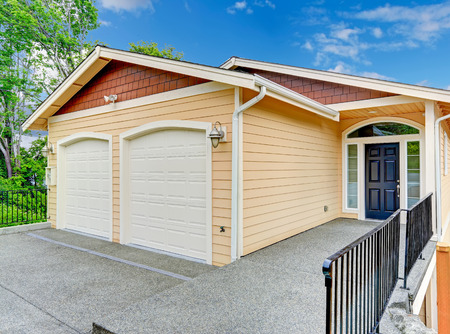 House exterior. Entrance porch with black door  and railings. House with two car garage Stock Photo