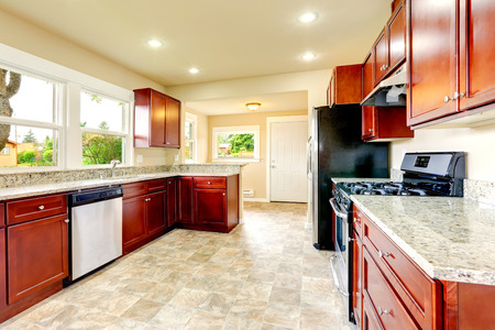 black appliances: Bright kitchen room with black and steel appliances, beige tile floor and bright storage combination