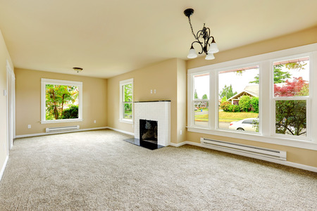 空の家のインテリア。アイボリーの壁と明るいグレーのカーペット床とファミリールーム。客室にはれんが造りの白い背景の暖炉 写真素材
