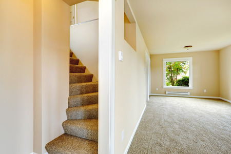 Empty house interior. Bright room with carpet floor and staircase with carpet steps Stock Photo