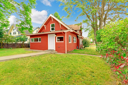Small coutnryside house exterior in bright red color with white trim. Front yard with lawn and trees
