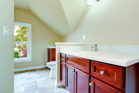 vaulted ceiling: Empty bathroom with vaulted ceiling. Bright color cabinet with clean white counter top and sink