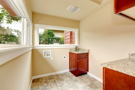 Soft tones laundry room wtih tile floor and cabinets. Empty space for laundry appliances Stock Photo